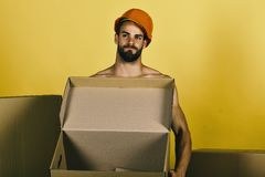 Sexuality and building concept: man standing naked with empty box royalty free stock photography