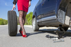 Sexually dressed woman repairing car Royalty Free Stock Photos