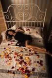 Sexuell brunett som ligger på ett underlag royaltyfri foto