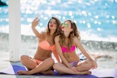 Sexuell flicka i en ljus bikini på en solig strand Bikini röda kanter, blått hav, brunbränd flicka Två vänner har att vila på arkivbilder