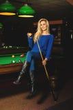Sexuelle Dame des Spaßes, die auf Billardtisch mit dem Stichwort und Ball in ha aufwirft Stockfotografie