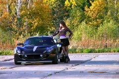 Sexuelle junge Frau, die nahe niedrigem Sportwagen steht lizenzfreies stockfoto