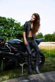 Sexuelle Radfahrerfrau mit ihrem Motorrad lizenzfreie stockfotografie