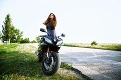 Sexuelle Radfahrerfrau mit ihrem Sportmotorrad stockfotos