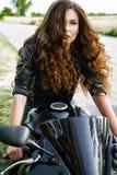 Sexuelle Radfahrerfrau mit ihrem Sportmotorrad lizenzfreies stockfoto