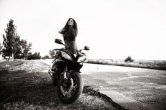 Sexuelle Radfahrerfrau mit ihrem Sportmotorrad stockbilder