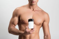 Sexueller Kerl steht mit Antitranspirationsmittel in seiner Hand lizenzfreies stockbild