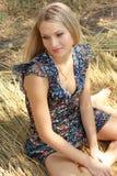 Sexuelles blondes Mädchen sitzt auf Weizen Stockbild