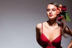 Sexuelles Mädchen im roten Kleid mit Blumen in ihrem Haar Lizenzfreie Stockbilder
