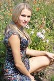 Sexuelles Mädchen sitzt im Park nahe Blumen Stockfoto