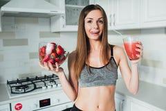 Sexuelles Sportmädchen, das einen köstlichen Smoothie mit Beeren trinkt Stockfotos