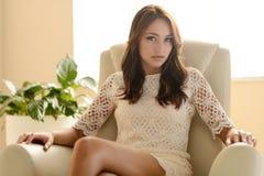 Sexy à la maison. Jeune femme sexy s'asseyant à la chaise et au regard images stock