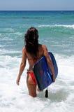 aantrekkelijke jonge vrouw die in rode bikini aan blauwe overzees op zonnig strand met lichaamsraad und opstapt Royalty-vrije Stock Foto