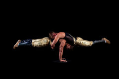 Sexy acrobats balancing, isolated on black Stock Images