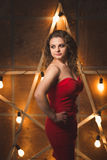 Actress in dress posing at big glowing star. Actress in red dress posing at big glowing star stock images