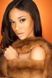 African American fashion model wearing fur. African American fashion model wearing a Vintage 50s Fox Fur Stole on orange background royalty free stock photos