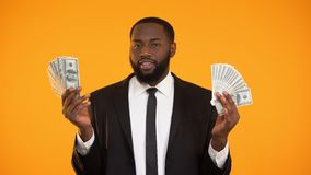 Sexy african-american male in suit playing with dollar banknotes and making kiss. Stock footage stock video