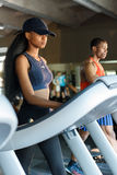 african american slim woman with her black handsome athletic trainer on the treadmill in gym. Fitness concept Stock Image