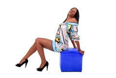 Sexy African American woman. Full length shot of a beautiful African American woman with great legs sitting on a blue stool, with her head back and her eyes Stock Photo