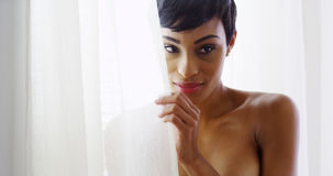 Sexy African American woman looking out window and smiling Royalty Free Stock Image