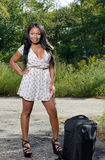 Sexy African-American woman in sundress with suitcase - travel Stock Image