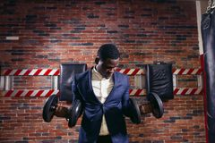 Healthy african man working out with dumbbells in gym. Sexy african man in classic suit working out with dumbbells in gym Stock Photos