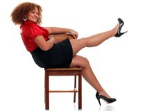 african woman on a chair lifting her leg Royalty Free Stock Photos