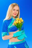 Sexy air stewardess with flowers. Hostess. Sexy beauty stewardess with yellow flowers in blue uniform on blue sky background Stock Photography