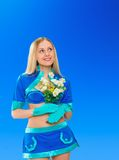 Sexy air stewardess with flowers. Hostess. Sexy beauty stewardess with yellow flowers in blue uniform on blue sky background Stock Photo