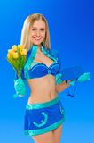Sexy air stewardess with flowers. Hostess. Sexy beauty stewardess with yellow flowers in blue uniform on blue sky background Royalty Free Stock Photos