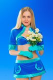 Sexy air stewardess with flowers. Hostess. Sexy beauty stewardess with yellow flowers in blue uniform on blue sky background Stock Photos