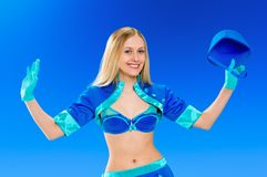 Sexy air stewardess. Hostess. Sexy beauty stewardess in blue uniform on blue sky background with cap in hand Stock Photography