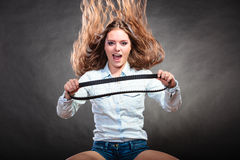 Sexy alluring woman holding fan belt. Feminism. Stock Photography