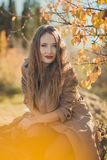 Amazing lady girl nifty stylish dressed in autumn jacket with blond hairs and pout red lips with make up face posing sit for. Camera in central park spring royalty free stock images