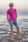 Sexy amincissez l'homme convenable de brune dans des shorts de blues-jean et le rose pourpre Photographie stock