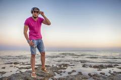 Sexy amincissez l'homme convenable de brune dans des shorts de blues-jean et le rose pourpre Image stock