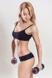 Sexy amincissez la femme blonde convenable dans les vêtements de sport avec des haltères musculeux Images stock