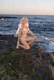 Sexy Angel Kneeling on Rocks Royalty Free Stock Photography