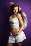 Sexy angel in the studio. Brunette posing as an angel in the studio with a violet background Stock Image