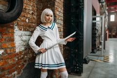 Anime style blonde lady with sword. Cosplay fashion, asian culture, doll with blade, cute woman with makeup in the factory shop royalty free stock photography