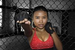 Sexy Asian fighter woman in fighting gloves and sport clothes inside MMA cage posing cool Stock Photo