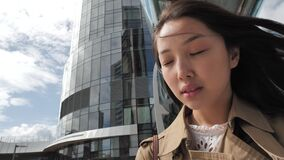 A girl with brown long hair poses in front of a skyscraper