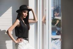 Asian woman akimbo near window. Sexy Asian model woman in black shirt wearing hat standing and akimbo near window with strong hard light royalty free stock photo