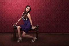 Sexy asian woman with purple dress sitting in sofa Royalty Free Stock Images