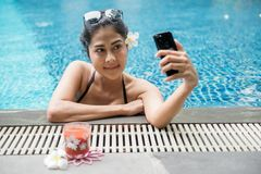 Sexy Asian woman selfie at swimming pool. Attractive sexy Asian woman with black two piece swimsuit and sunglasses selfie herself by smartphone nearat swimming Royalty Free Stock Images