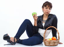 Asian woman sits next to a fruit basket Stock Images