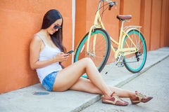 Sexy asian woman sitting near the wall and vintage bicycle Royalty Free Stock Image