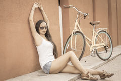 Sexy asian woman sitting near the wall and vintage bicycle Royalty Free Stock Photography