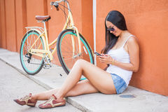 Sexy asian woman sitting near the wall and vintage bicycle Stock Photos