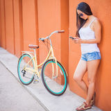 Sexy asian woman standing near the wall and vintage bicycle Stock Images